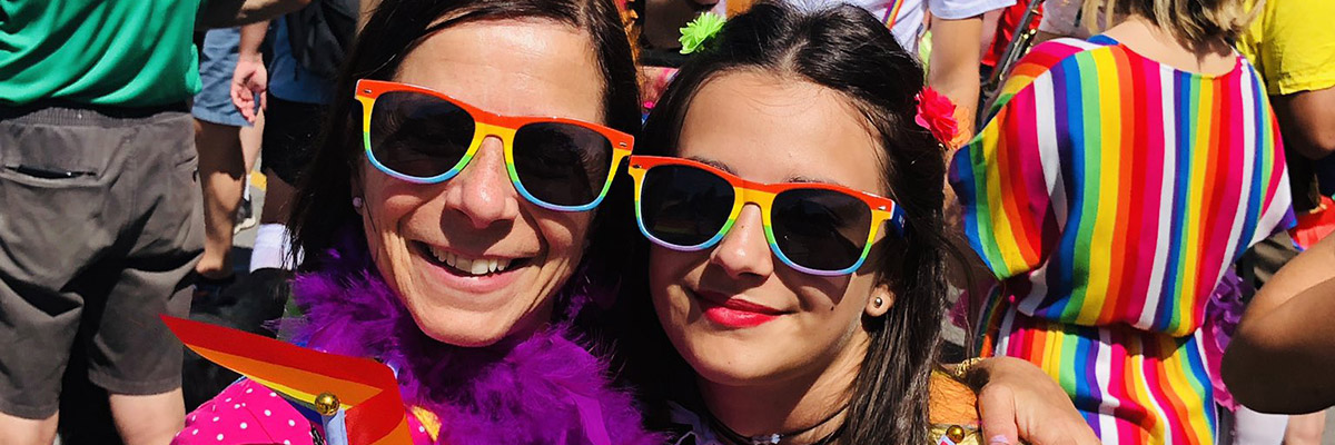 Two women with pride flags smiling at the parade
