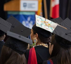 A colourful graduation cap stands out in a sea of black caps