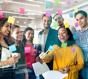A group of people gathered in front a glass with sticky notes