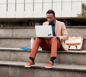 A man sitting on the steps working his laptop