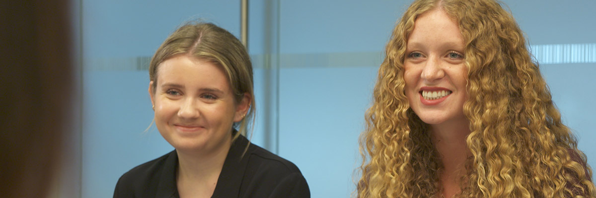 Two young women participate in a roundtable discussion