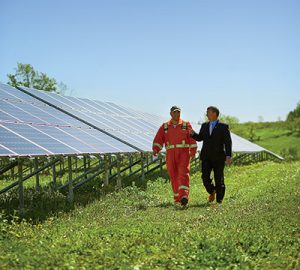 Two people walking with solar panels in the background