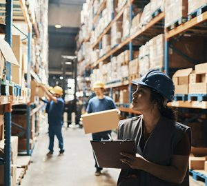 A woman wearing a hard hat takes inventory on a clipboard