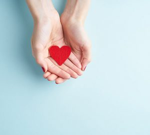 A pair of hands holding a red heart