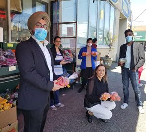 People with masks practising physical distancing outside a grocery store