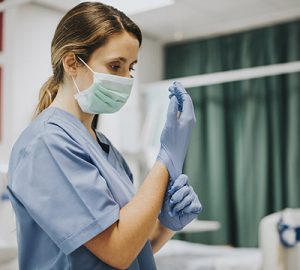 A healthcare worker with a mask is putting on gloves