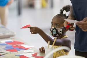 A little girl with a mask helps with the mural